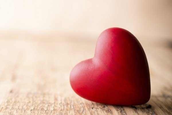 Red heart-shaped candy on a wooden background.